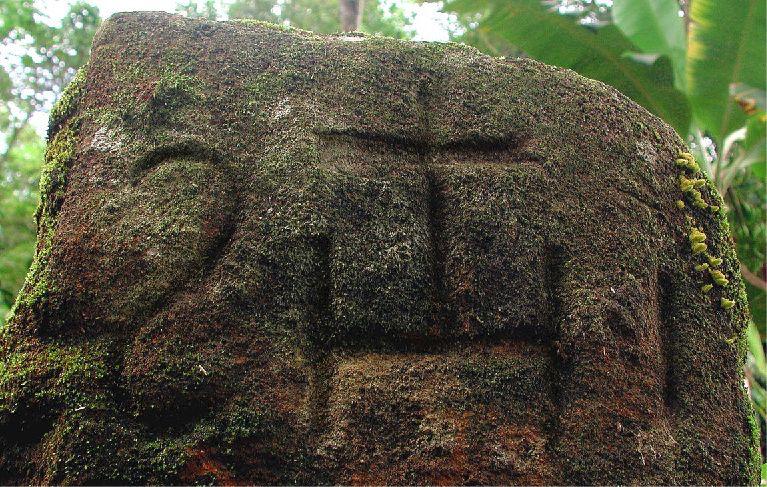 Borne d'arpentage en pierre de l'habitation Loyola marquée du monogramme de l'ordre des Jésuites; ici, les lettres IHS surmontées d'une croix sont gravées en miroir.